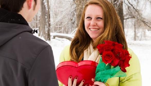 Junge Frau hält rote Rosen und ein Schokoladenherz in Händen © arinahabich, Fotolia.com