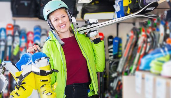Frau mit Skihelm hält Skier auf der Schulter und Skischuhe in der Hand © JackF, stock.adobe.com