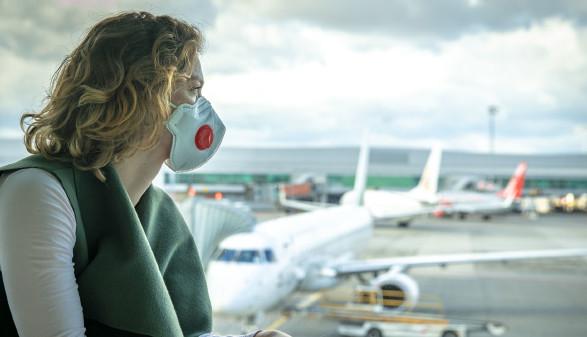Frau mit Mundschutz blickt auf Flughafen © edojob , stock.adobe.com