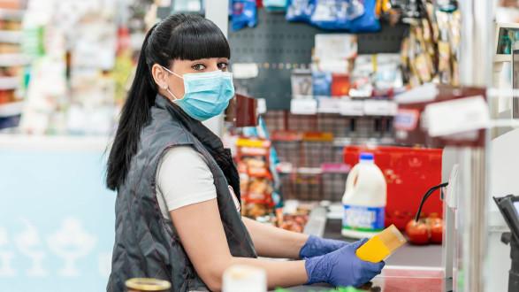 Kassiererin mit Schutzmaske und Handschuhe bei Supermarktkassa © STEKLO_KRD , stock.adobe.com