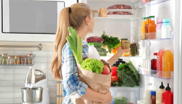 Frau mit Lebensmittel auf dem Arm steht vor dem geöffneten Kühlschrank © New Africa, stock.adobe.com