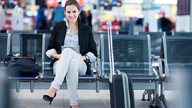 Frau sitzt am Flughafen mit Rollkoffer. © lightpoet, Fotolia