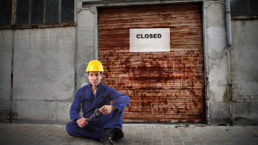 Arbeiter sitzt vor verschlossenem Firmentor © olly, stock.adobe.com