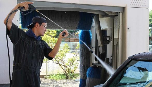 Arbeiter reinigt mit Wasser das Auto bevor es in die Waschstraße fährt © buritora, stock.adobe.com