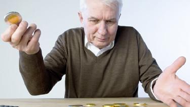 Alter Mann hält Münze in der Hand und schaut auf weitere Münzen die am Tisch liegen. © stock4you, Fotolia.com