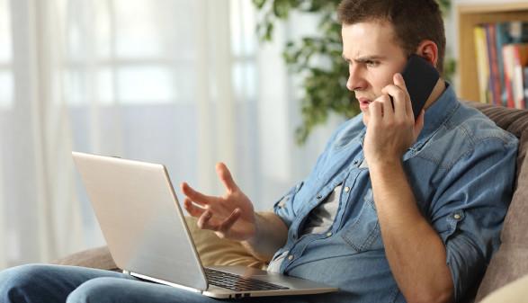 Mann sitzt vor Laptop und beschwert sich per Telefon © Antonioguillem, stock.adobe.com