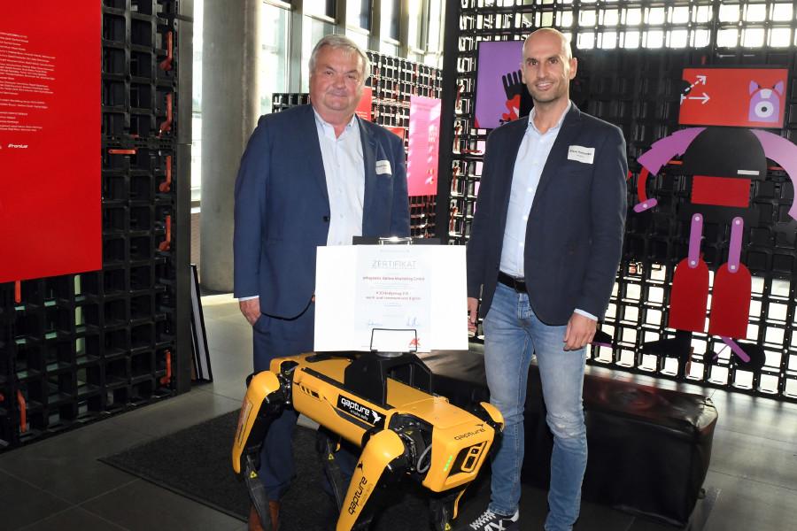 AK-Präsident Dr. Johann Kalliauer (link) übergibt mit Roboterhund Spot das Zertifikat an eMagnetix-Geschäftsführer Klaus Hochreiter. © Wolfgang Spitzbart, AK OÖ
