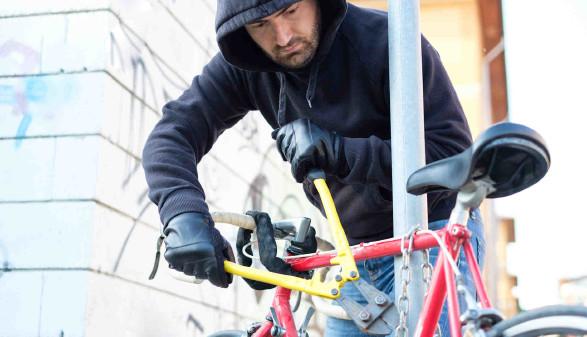 Mann mit Kapuzenpulli schneidet ein Fahrradschloss mit einem Bolzenschneider durch © Paolese, stock.adobe.com