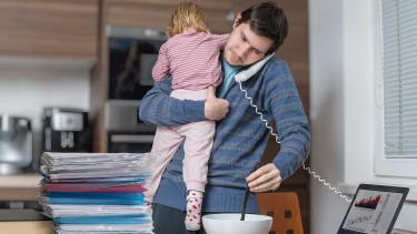 Vater arbeitet mit Kind am Arm © vchalup, stock.adobe.com