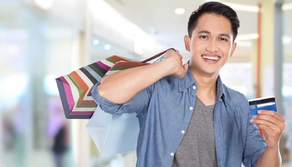 Junger Mann mit Einkaufstaschen und Kreditkarte in der Hand © Odua Images, stock.adobe.com