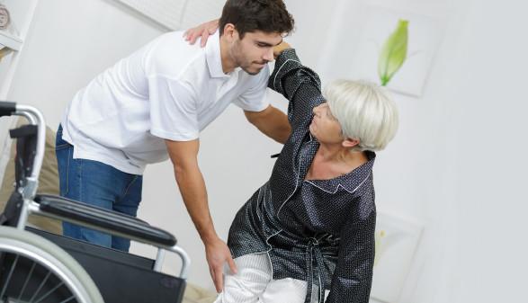 Pfleger hilft Dame in den Rollstuhl © auremar , stock.adobe.com