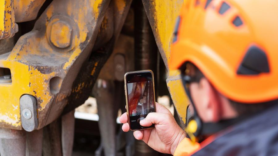 Arbeiter macht mit Handy Foto von Baumaschine © -, Plasser & Theurer Export von Bahnbaumaschinen GmbH