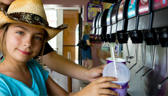 Mädchen hält Becher unter Getränkeautomat © Eléonore H , stock.adobe.com