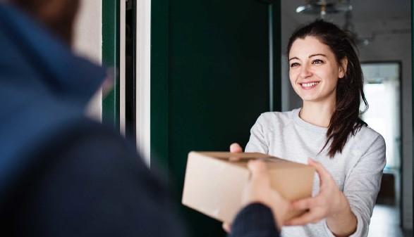 Junge Frau übernimmt ein Paket vom Zusteller © Halfpoint, stock.adobe.com