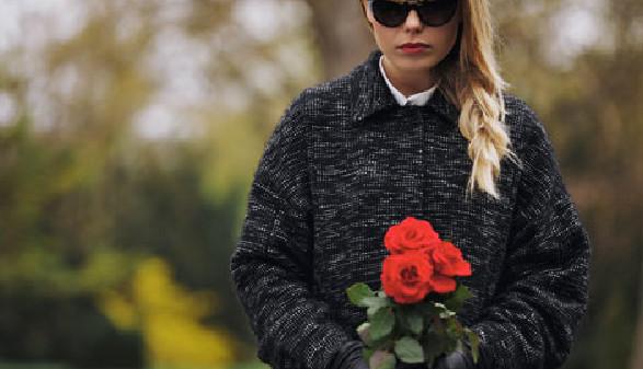 Junge Frau mit Sonnenbrille und roten Rosen am Friedhof © Ammentorp, Fotolia.com