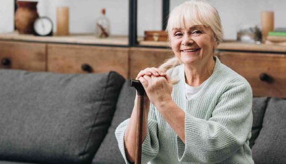 Ältere Frau mit Stock sitzt auf dem Sofa © LIGHTFIELD STUDIOS, stock.adobe.com