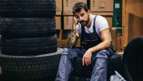 Arbeiter in Arbeitskleidung sitzt auf Autoreifen und wartet © dusanpetkovic1, stock.adobe.com