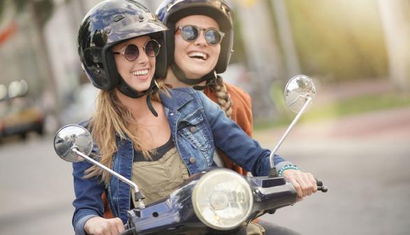 Zwei Mädchen sitzen am Moped und haben Spaß © goodluz, stock.adobe.com
