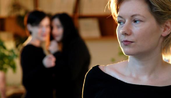 Zwei junge Frauen im Bildhintergrund tuscheln über Frau © Gernot Krautberger, Fotolia