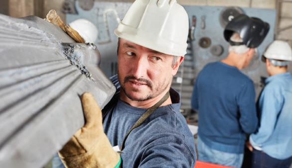Arbeiter mit Schutzhelm trägt Metallteil © Robert Kneschke , stock.adobe.com