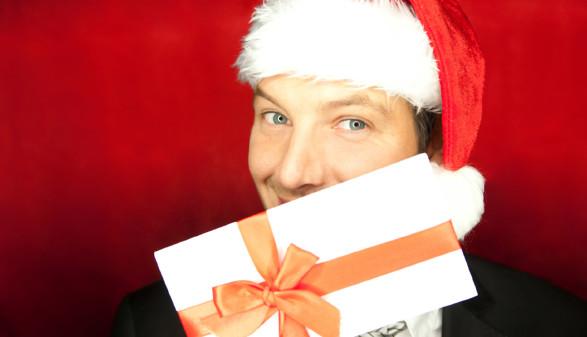Mann mit Weihnachtsmütze hält Geschenkgutschein vor Gesicht © detailblick-foto, stock.adobe.com