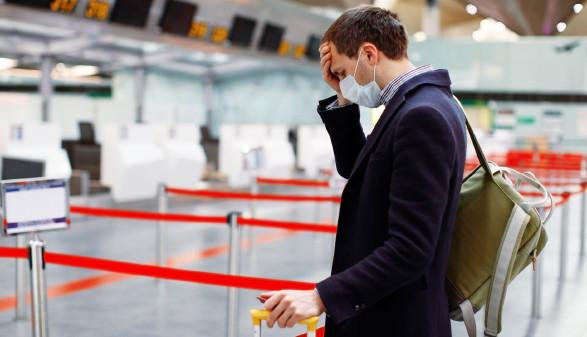 Mann steht mit Koffer am Flughafen beim CheckIn © Evgenia, stock.adobe.com