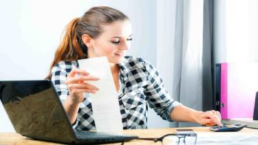 Frau sitzt vor Laptop und kalkuliert eine Rechnung mit dem Tischrechner © leszekglasner, stock.adobe.com