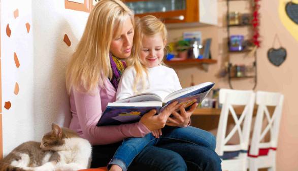 Mutter und Kind beim Vorlesen - mit Katze auf der Ofenbank © kzenon, stock.adobe.com