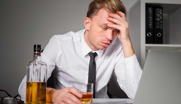 Mann trinkt im Büro Alkohol © Kaspars Grinvalds, stock.adobe.com