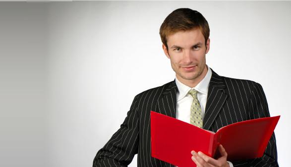 Mann in Anzug hält rote Mappe © Aphotostudio, stock.adobe.com