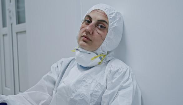 Arbeitnehmerin mit Corona-Schutzausrüstung © procinemastock , stock.adobe.com