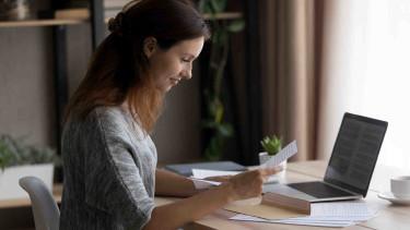 Frau sitzt vor Laptop und liest einen Vertrag © fizkes, stock.adobe.com