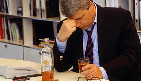 Mann sitzt mit einer Flasche Alkohol beim Schreibtisch © Udo Kroener, Fotolia