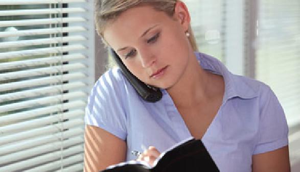 Frau telefoniert und notiert währenddessen im Notizbuch © auremar, Fotolia.com