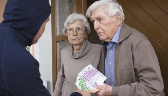 Seniorenpaar übergibt Geld an der Haustür © lettas, stock.adobe.com