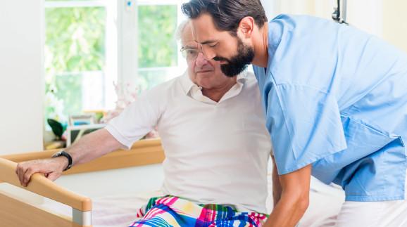 Junger Mann hilft älterem Herren aus dem Bett © Kzenon, stock.adobe.com