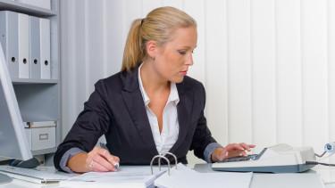 Frau sitzt bei Unterlagen und führt Berechnungen durch © Gina Sanders, stock.adobe.com