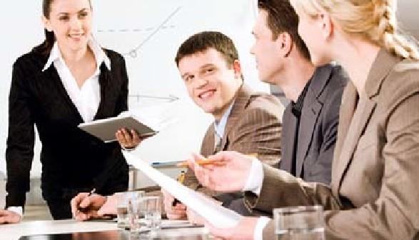 Junge Frau steht und spricht zu Kollegen die sitzen. © pressmaster, Fotolia.com