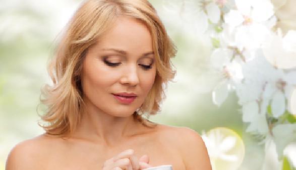 Frau hält Cremetigel in der Hand - im Hintergrund befinden sich Blütenzweige © Syda Productions, Fotolia.com