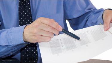 Mann mit Krawatte zeigt mit Kugelschreiber auf Bilanz © ArTo , stock.adobe.com