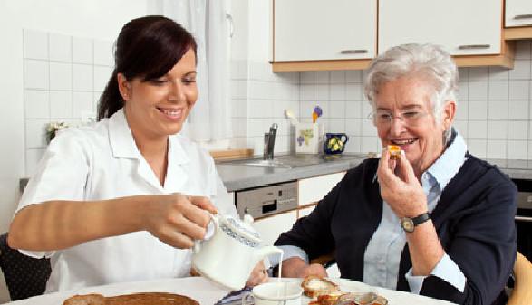 Heimhelferin sitzt mit älterer Frau beim Frühstückstisch © Gina Sanders, Fotolia.com
