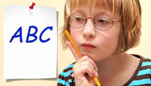 Schülerin hält einen Bleistift in der Hand und denkt nach. Auf der Wand hängt ein A4-Blatt mit der Aufschrift ABC © K.-U. Häßler, Fotolia