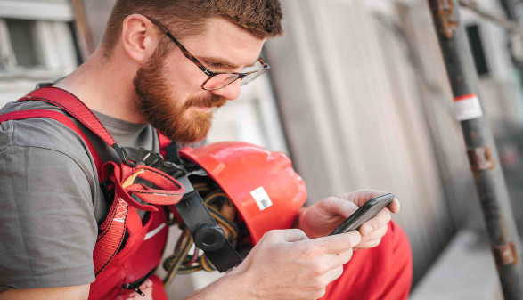 Bauarbeiter auf einem Gerüst mit Handy © guruXOX, stock.adobe.com