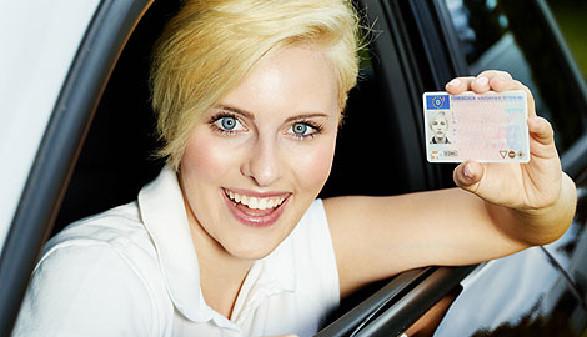 Lächelnde junge Frau mit Führerschein in der Hand © Karin & Uwe Annas, Fotolia.com