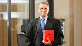 Anwalt mit Brille hält Gesetzbuch © Kzenon, stock.adobe.com