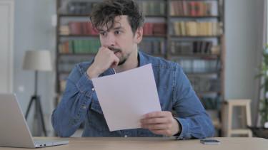 Nachdenklicher Mann sitzt mit Zettel vor Notebook © Mustansar, stock.adobe.com