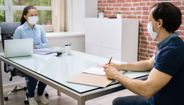 Besprechung im Büro mit Mund-Nasen-Schutz und Sicherheitsabstand © Andrey Popov, stock.adobe.com