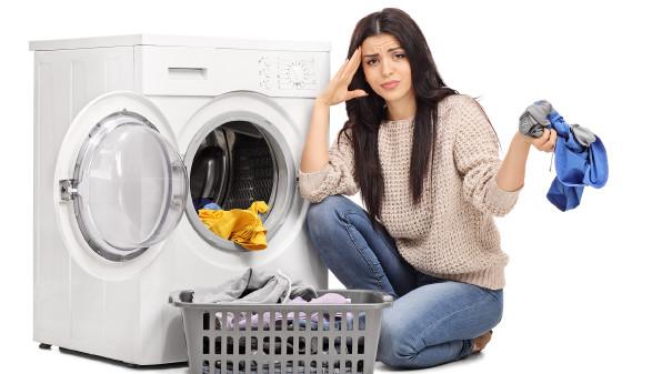 Frau sitzt vor Wäschekorb und Waschmaschine © Ljupco Smokovski , stock.adobe.com