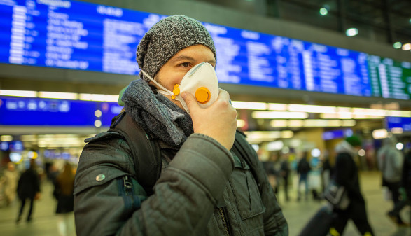 Mann mit Mundschutz in einer Flughafen-Halle © TeamDaf, stock.adobe.com