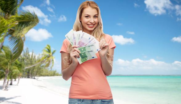 Junge Frau mit Geldscheinen, im Hintergrund Palmenstrand © Syda Productions, Fotolia.com